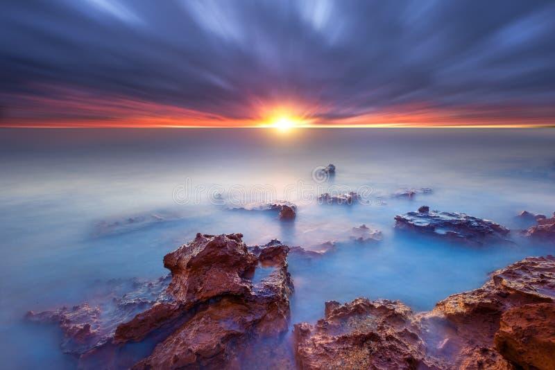 在海湾的日落岩石 库存图片