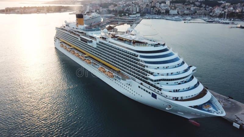 在海湾的美丽的白色巡航划线员,鸟瞰图 ?? 港口、海岸和大游轮的美丽如画的看法 图库摄影