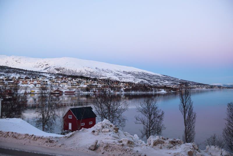 在海湾附近的典型的挪威五颜六色的被绘的房子在Tromsø附近 免版税库存图片