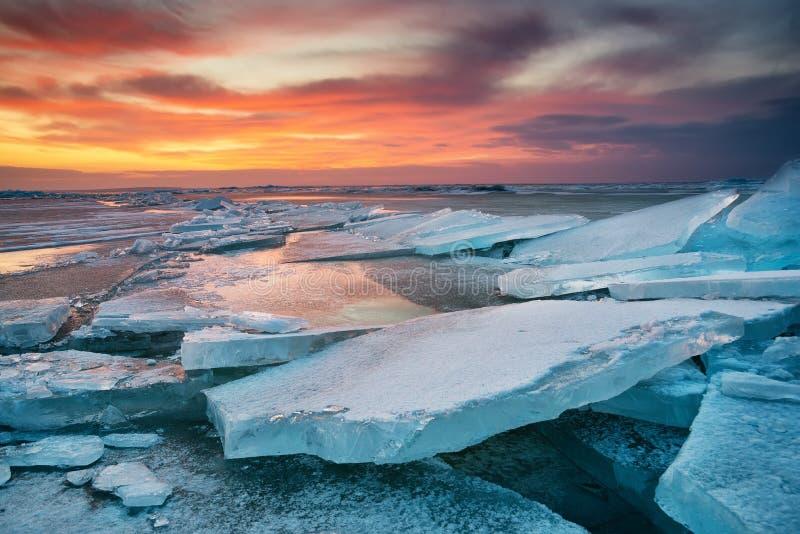 在海滨的冬天风景在日落期间 Lofoten海岛,挪威 冰和日落天空 免版税库存图片
