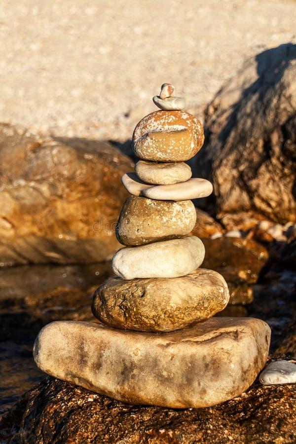在海滨的小卵石栈 石头金字塔在海滩的 在日落的光 耐心的标志 和谐和平衡的概念 库存照片
