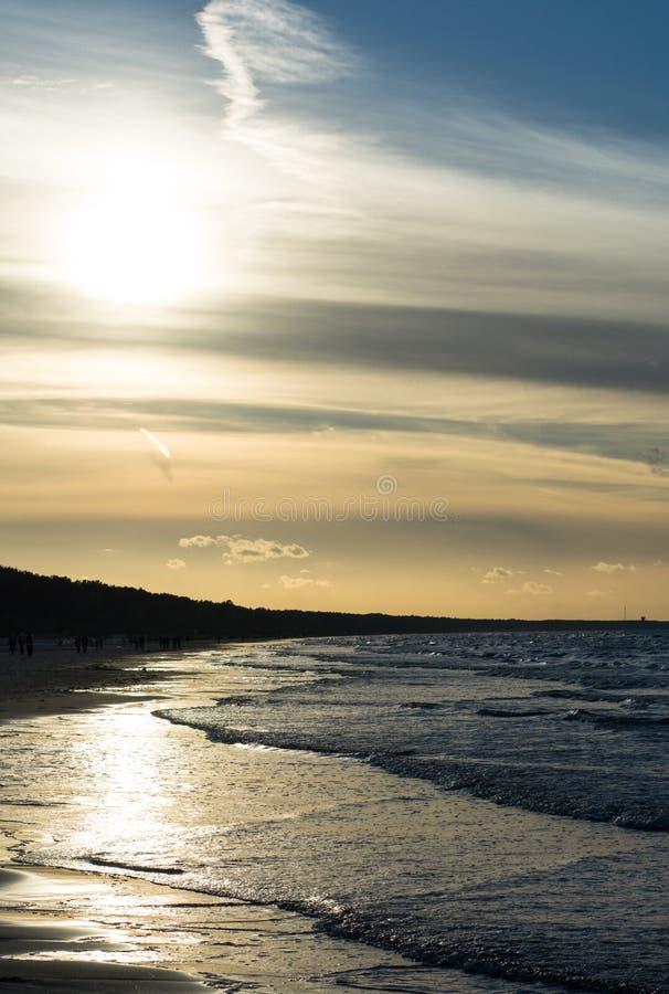 在海滨的日落与人 免版税图库摄影