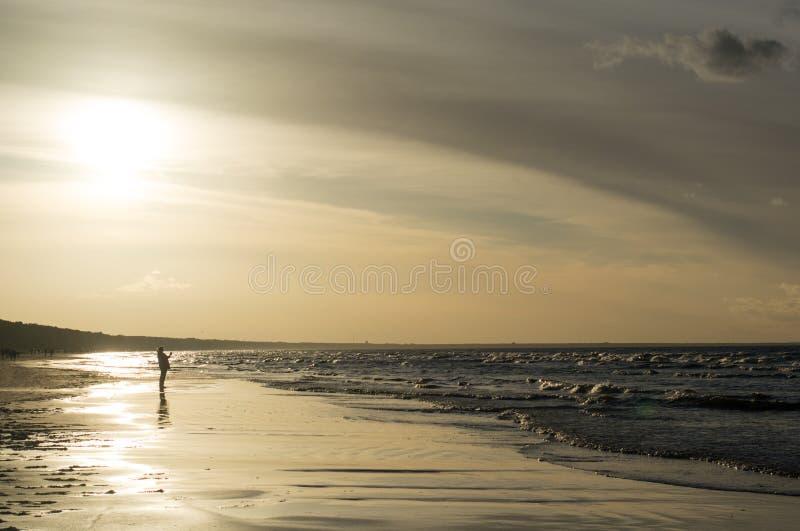 在海滨的日落与人 图库摄影