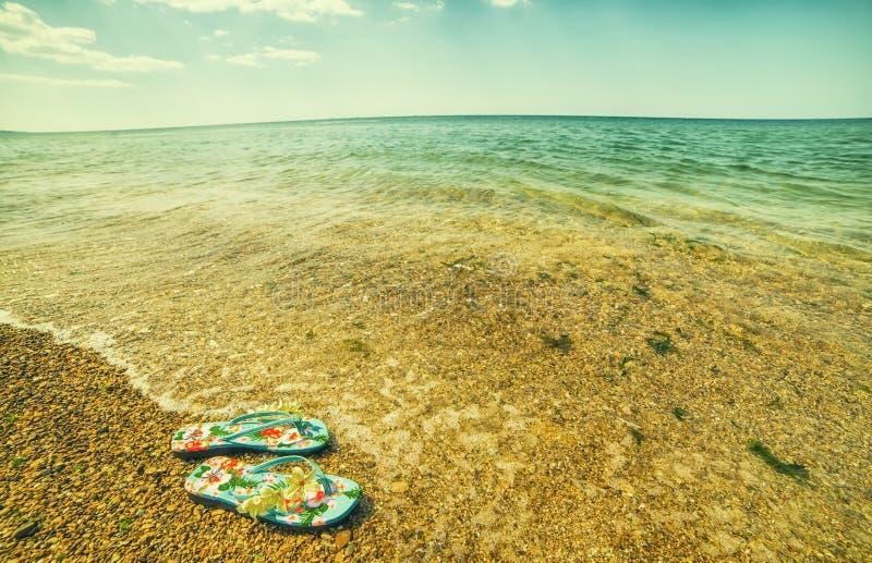 在海滨的海滩拖鞋 晴朗的热的天,一个离开的海滩, 库存图片