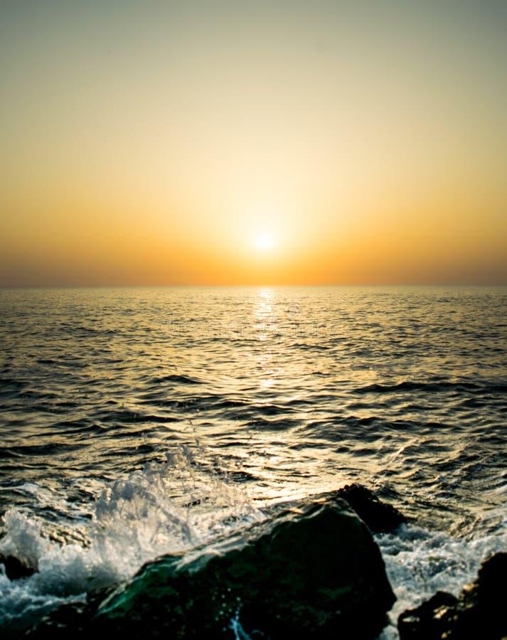 在海滨的美好的日出 海的波浪击中了驱散水的岩石 太阳它的在a的露面 库存图片