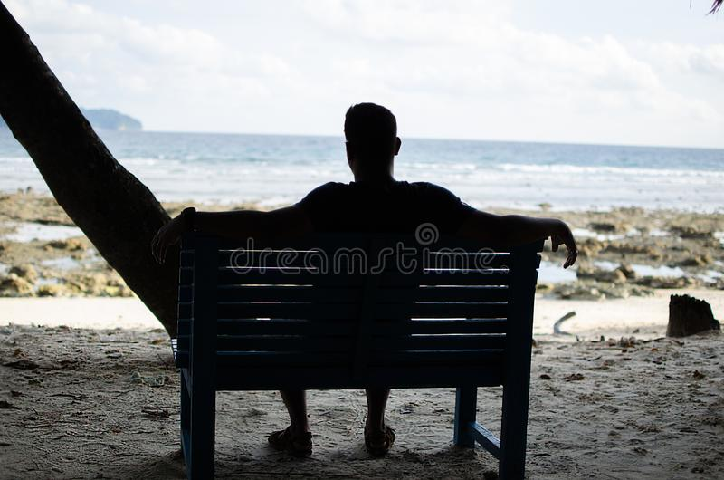 在海滨附近供以人员单独坐长凳 库存图片