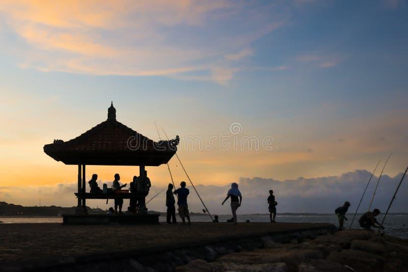 在海滩、剪影小屋和一些人的日落 库存图片