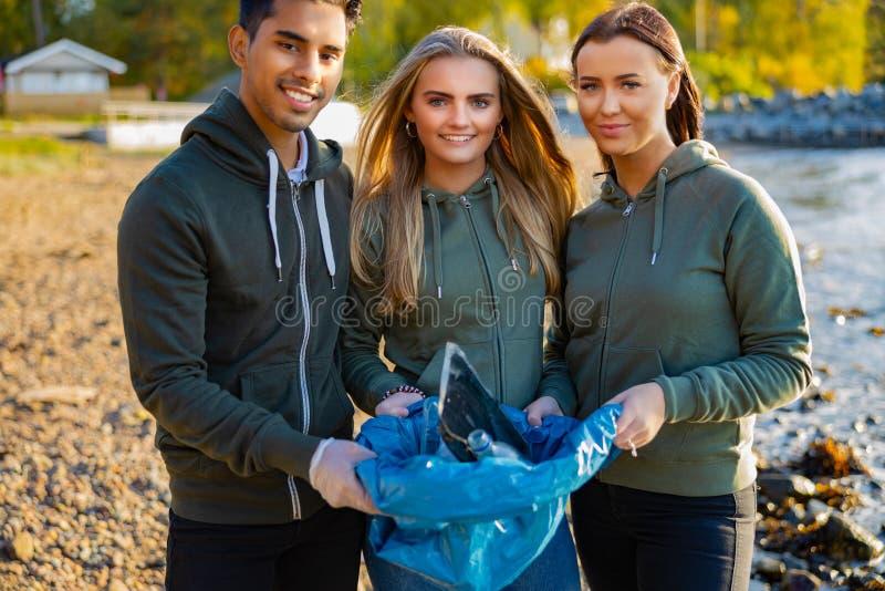 在海滩上拿着垃圾袋的微笑志愿者 免版税库存图片