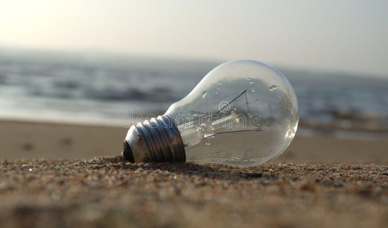 在海滩下落的电灯泡 库存照片