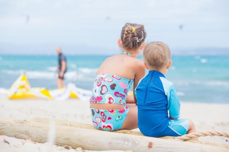 在海滩假期的男孩和女孩 库存图片