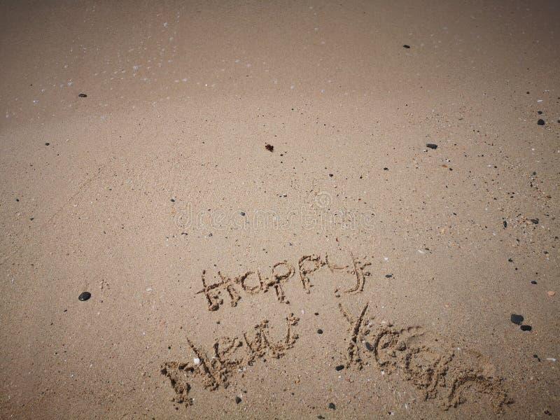 在海滩写的新年快乐 库存图片