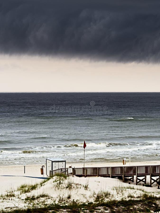 在海滩和木走道的暴风云 库存图片