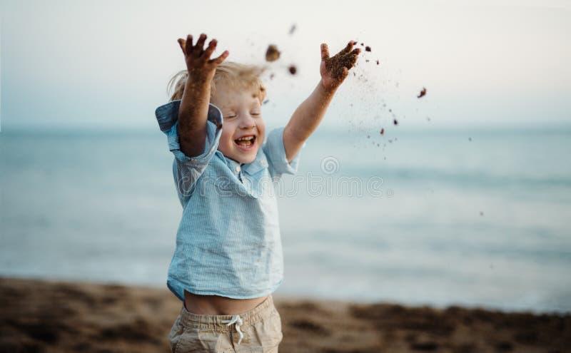 在海滩在度假夏天休假,投掷的沙子的一个小小孩男孩身分 免版税库存照片