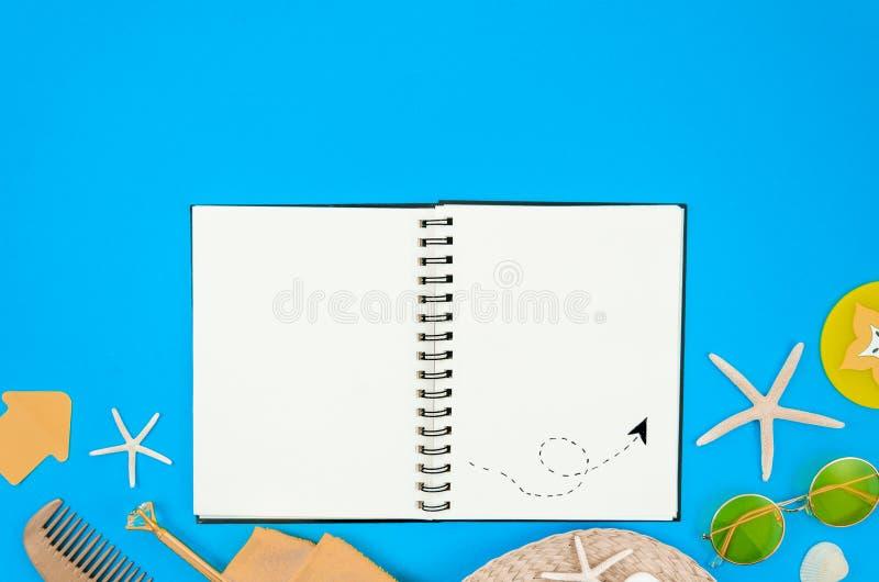 在海滩大模型的旅行日志 顶视图在蓝色背景的螺旋笔记薄与太阳镜和海星 r 图库摄影