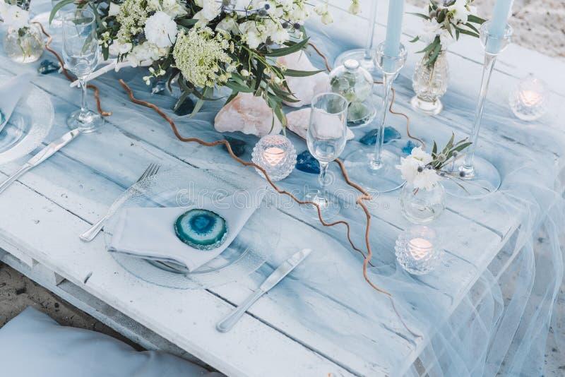 在海滩婚礼的蓝色柔和的淡色彩设定的典雅的桌 免版税库存图片