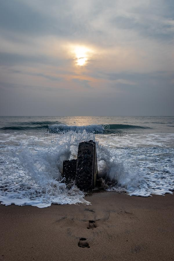 在海滩岩石的水飞溅有日出视图 免版税库存照片