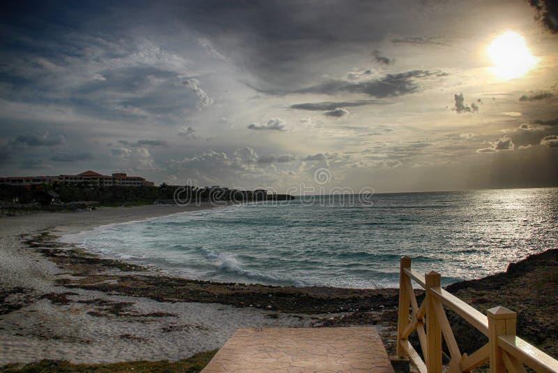 在海滩巴拉德罗角的日落在古巴 有金太阳和大西洋清楚的水  有长的沙滩 库存图片