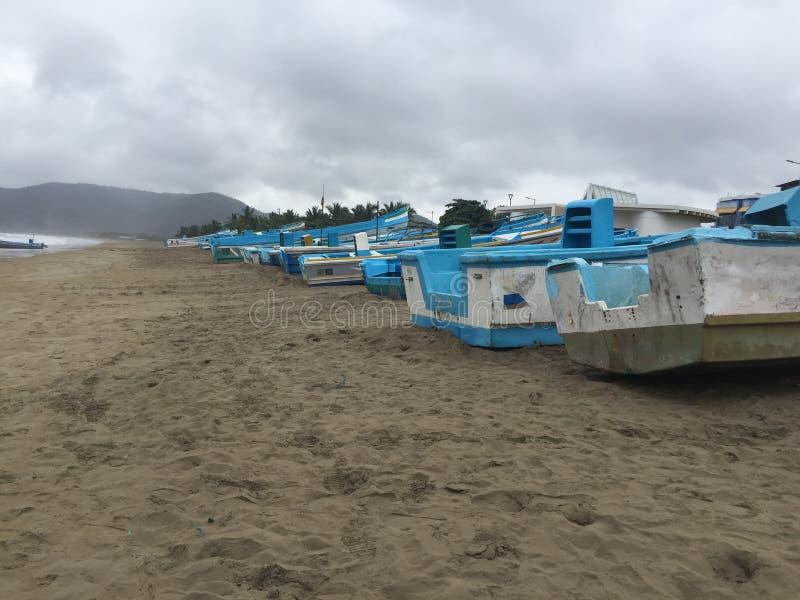 在海滩排队的许多老蓝色和白色渔船 图库摄影
