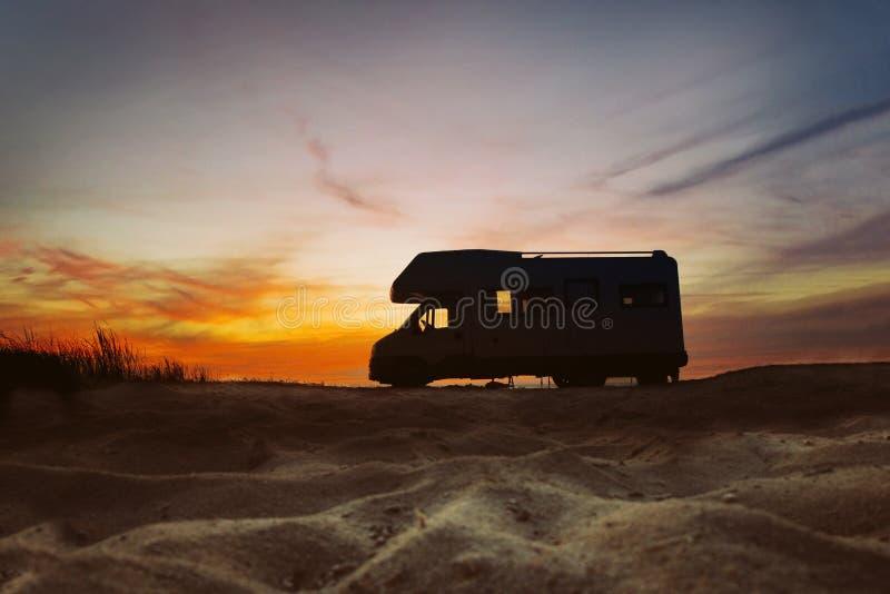 在海滩旁边停放的露营者货车 日落在背景中 夏天旅行的概念 库存照片