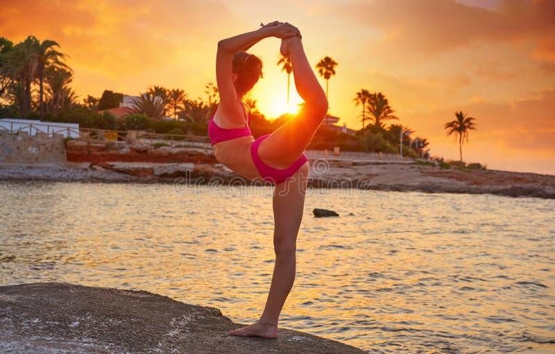 在海滩日落体操的女孩剪影 免版税库存照片