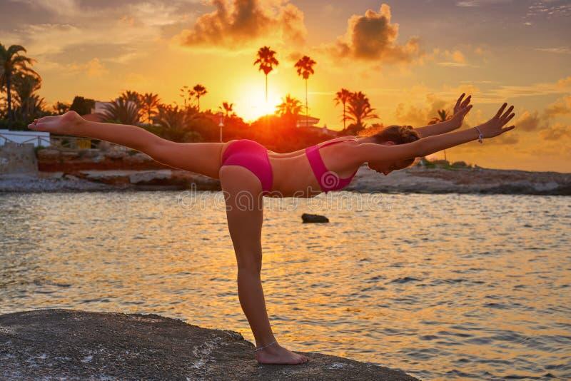 在海滩日落体操的女孩剪影 免版税库存图片