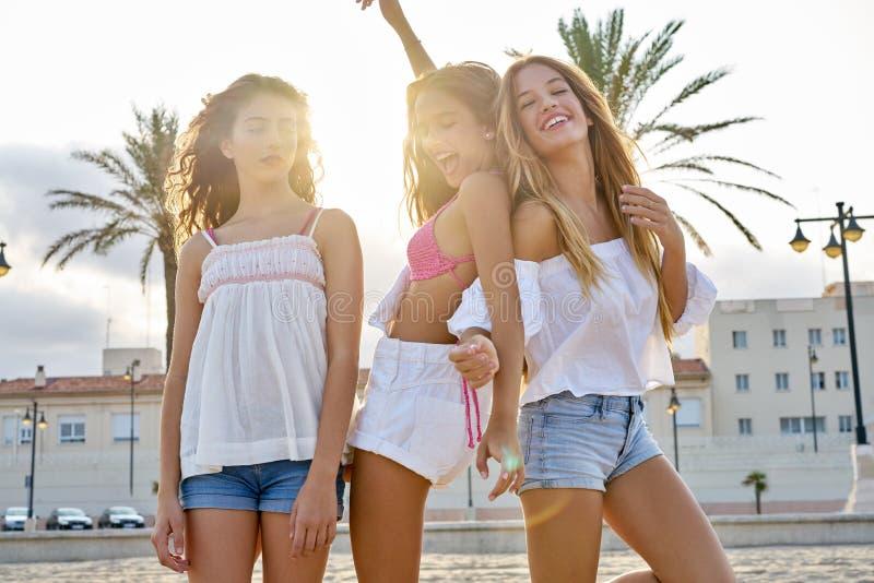 在海滩日落的最好的朋友青少年的女孩乐趣 免版税库存图片