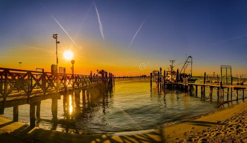 在海滩日落的葡萄酒木码头, Lido二耶索洛,威尼斯 免版税库存图片