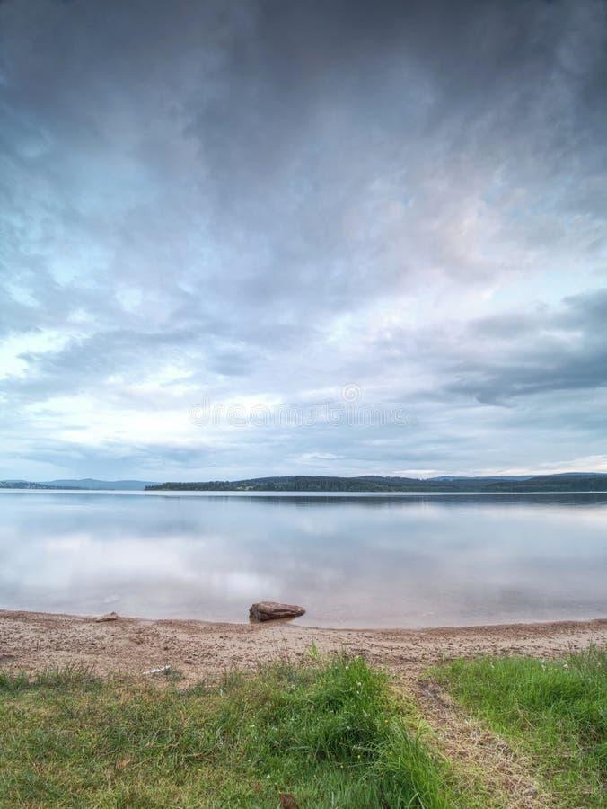 在海滩沙子的一块孤立石头接近湖水的 E 免版税图库摄影