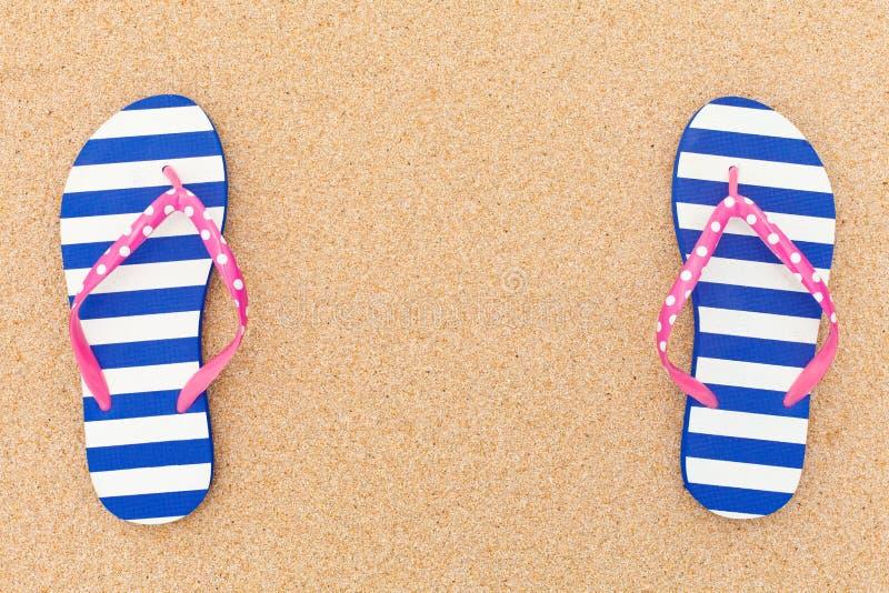 在海滩沙子的五颜六色的塑胶人字平底拖鞋对 免版税库存照片