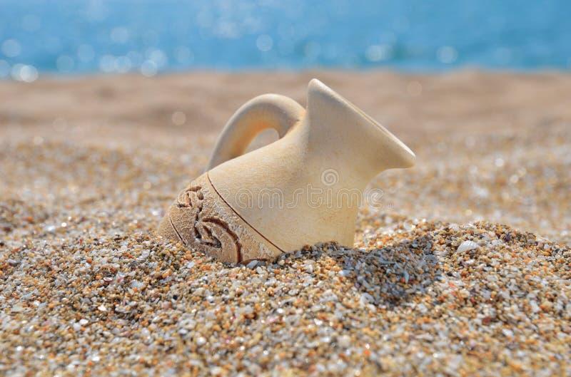 在海滩沙子的古老油罐 库存照片