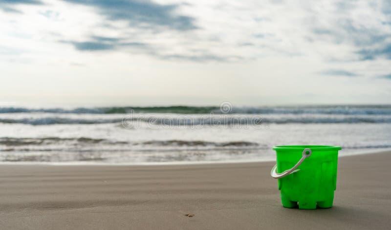 在海滩沙子的绿色桶 免版税库存图片