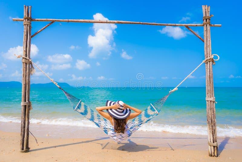 在海滩海和海洋的画象美好的年轻亚洲妇女幸福微笑休闲 免版税库存照片