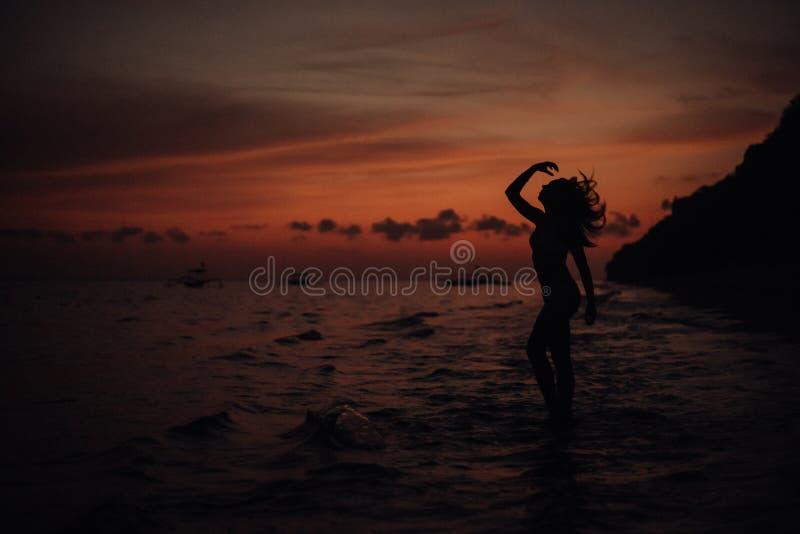 在海滩的一个少女立场 - 关于人、生活方式和体育的概念 剪影 库存照片