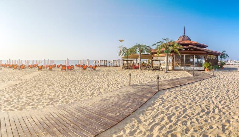 在海滩的一个酒吧与椅子和伞在一个美丽的海滩在日出在晴朗的海滩在保加利亚的黑海海岸 免版税库存照片