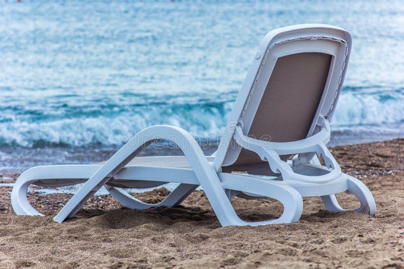在海滩的一张躺椅在蓝色海附近,特写镜头 图库摄影