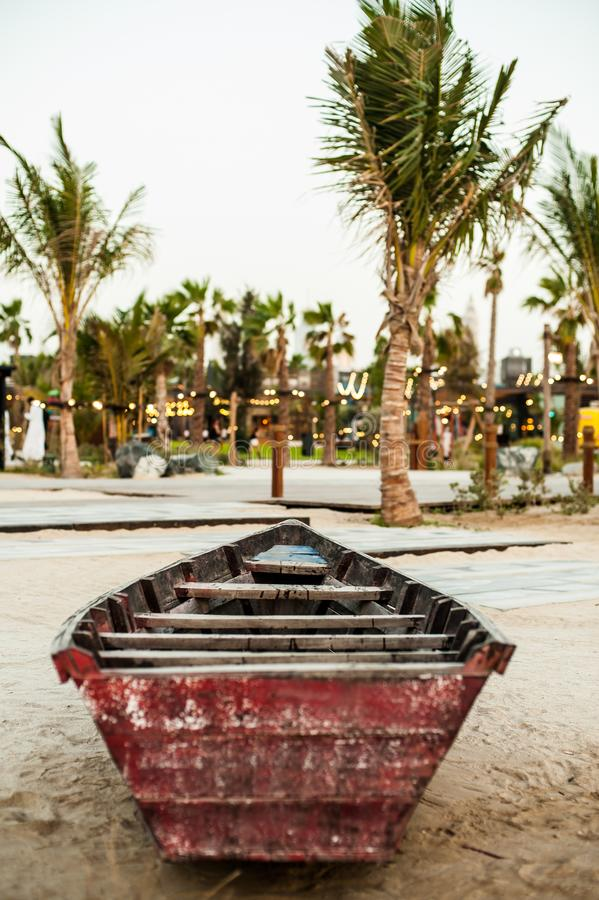 在海滩的一条老木小船在棕榈树下 库存图片