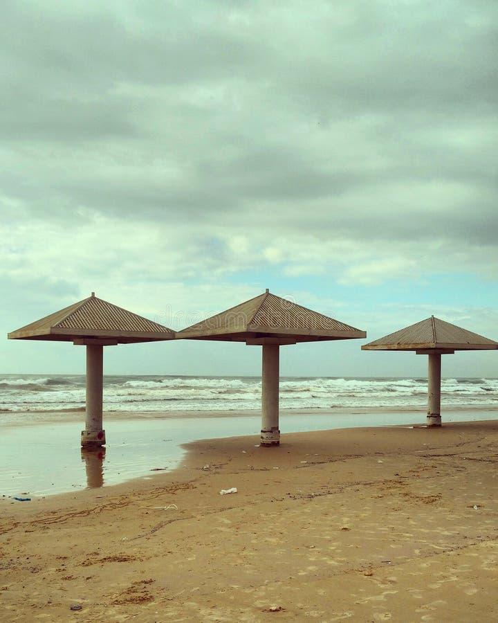 在海滩的三把伞 库存图片