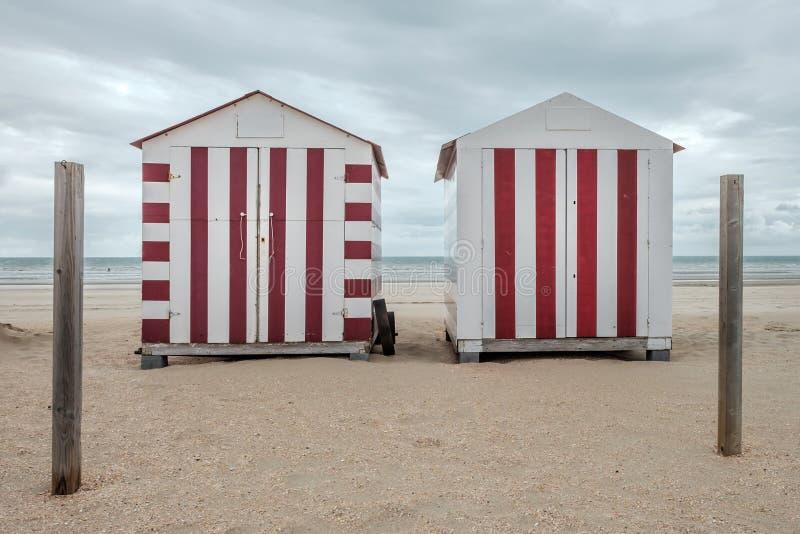在海滩的两个五颜六色的小屋 免版税库存图片