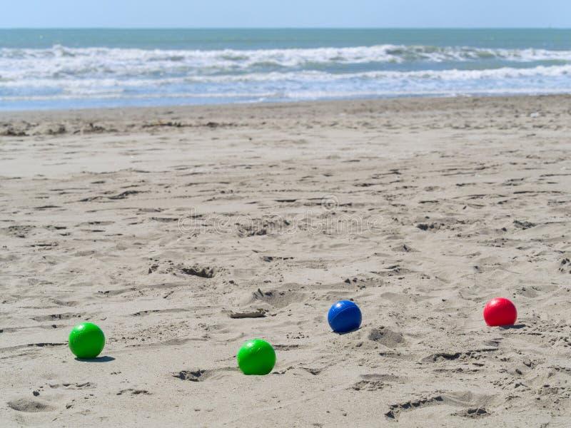 在海滩的五颜六色的塑料碗用于演奏petanque boul 库存图片