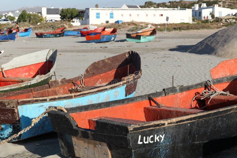 在海滩的五颜六色的渔船在Paternoster,有食家餐馆的小渔村南非的西海岸的 库存照片