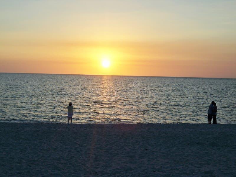 在海滩的人观看的日落 免版税库存图片