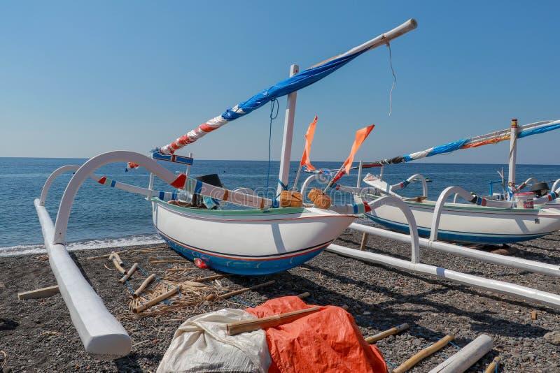 在海滩的传统巴厘语渔夫渔船与黑火山的沙子 与天空蔚蓝的好日子在热带天堂 f 免版税库存图片