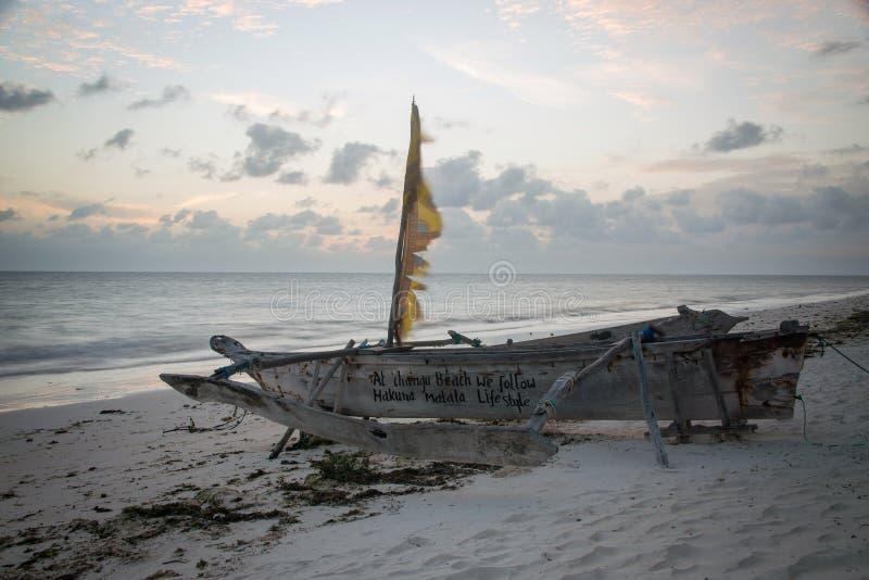 在海滩的传统木小船单桅三角帆船桑给巴尔在黎明 免版税库存图片
