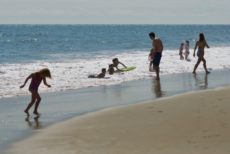 在海滩的儿童游戏在海浪 图库摄影