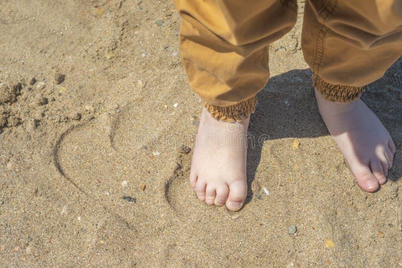 在海滩的光秃的儿童的脚 r 库存图片