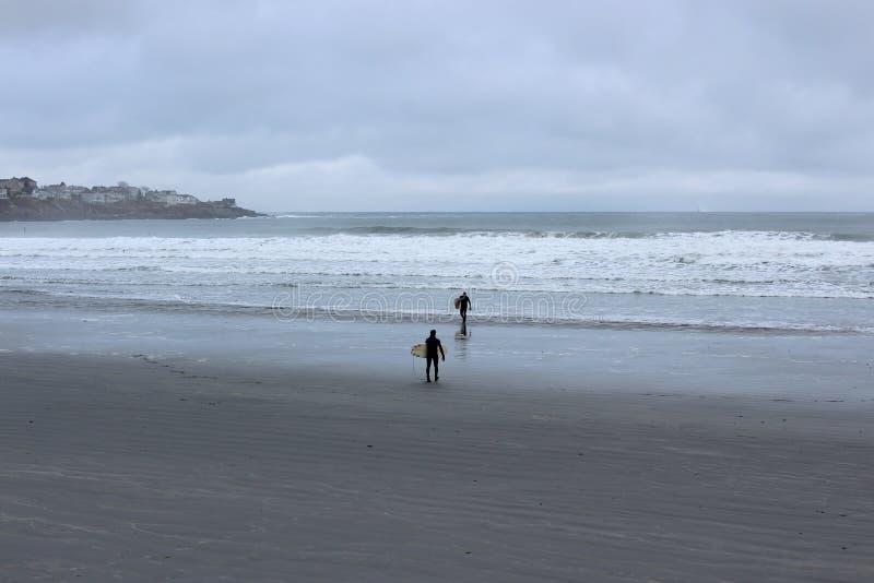 在海滩的冷的早晨,与准备好两位的冲浪者使乘波浪,约克,缅因,2018年 库存照片