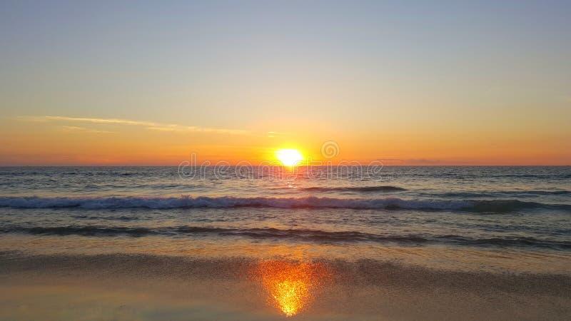 在海滩的反射日落 库存图片