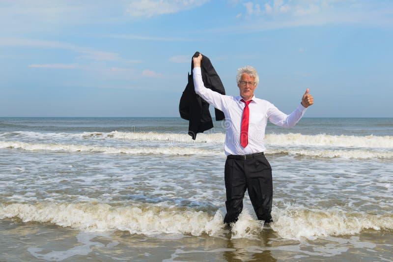 在海滩的商人身分 免版税库存照片