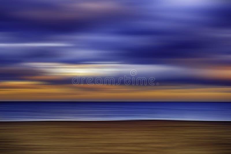 在海滩的多云日落,行动迷离 库存照片