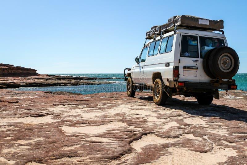 在海滩的大白色越野车 免版税库存图片